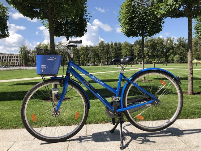 Blue city bike with a basket in the background of the park in Vilnius