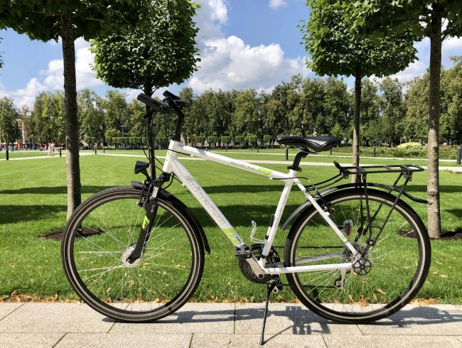 Hybrid bike Minevra in the background of the park in Vilnius for rent